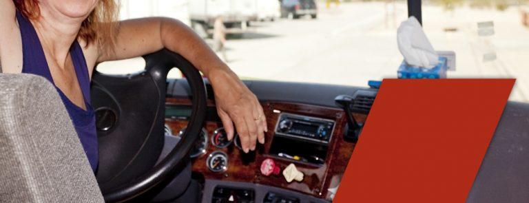 woman truck driver at wheel wondering if truck driving schools teach manual